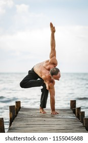 Young yoga trainer practicing yoga exercises on a wooden pier on a sea or river shore. Healthy lifestyle concept