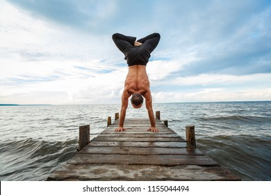 Young yoga trainer practicing handstand with a lotus on a wooden pier on a sea or river shore.Healthy lifestyle concept
