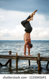 Young yoga trainer practicing handstand with legs crossed on a wooden pier on a sea or river shore. Healthy lifestyle concept