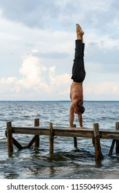 Young yoga trainer practicing handstand on a wooden pier on a sea or river shore.Healthy lifestyle concept