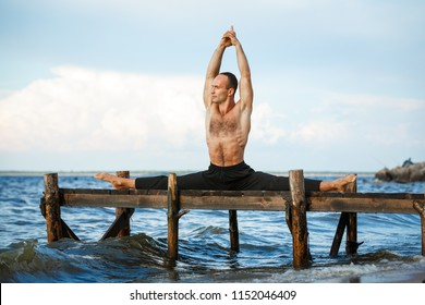 Young yoga trainer practicing samakonasana pose on a wooden pier on a sea or river shore. Healthy lifestyle concept