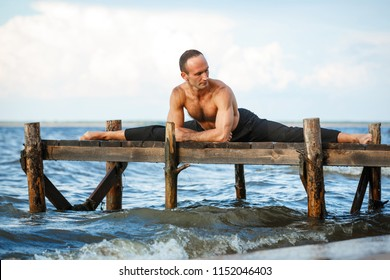 Young yoga trainer practicing split exercises on a wooden pier on a sea or river shore. Healthy lifestyle concept