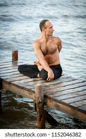 Young yoga trainer practicing twist yoga exercises on a wooden pier on a sea or river shore. Healthy lifestyle concept