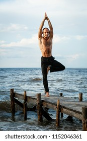 Young yoga trainer practicing Vrikshasana or tree pose on a wooden pier on a sea or river shore. Healthy lifestyle concept