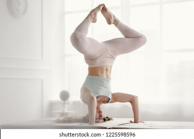 Young yoga woman doing handstand with folded legs