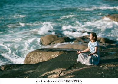 Young yoga woman meditates in the lotus position sitting on rocks on the Atlantic ocean coast.