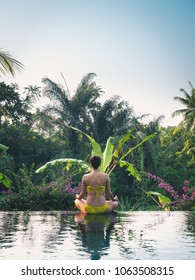 Young yoga woman meditating in yellow bikini sitting on the edge of Infinity pool in jungles in Ubud, Bali island in Indonesia. Vertical image.