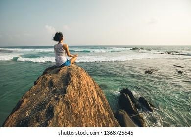 Young yoga woman meditation on seaside rock cliff edge