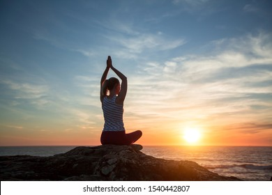 Young yoga woman meditation on the ocean beach at amazing sunset.