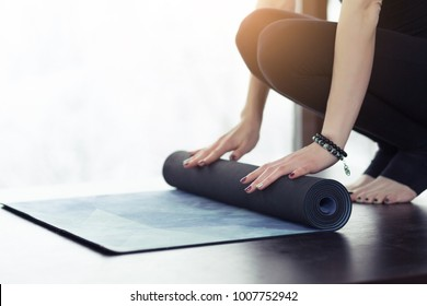 Young yoga Woman rolling her violet mat after a yoga class on wooden floor near a window, close up