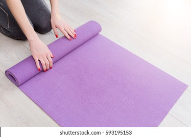 Young yoga Woman rolling her lilac mat after a yoga class on wooden floor near a window, close up