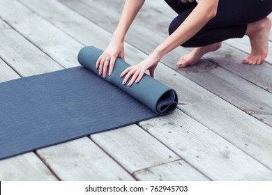 Young yoga woman rolling her black mat after a yoga class on wooden floor near outdoors, close up