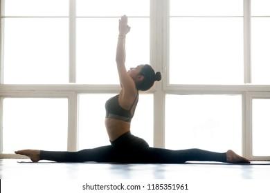 Young yogi attractive woman practicing yoga, doing Monkey God exercise, Splits, Hanumanasana pose, working out, wearing sportswear, grey pants, top, indoor full length, at yoga studio, side view