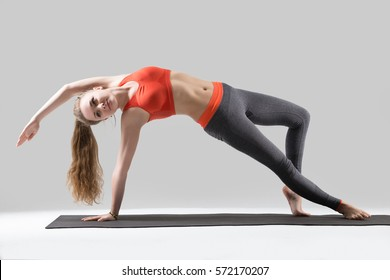 Young yogi attractive woman practicing yoga, doing Wild Thing, Flip-the-Dog exercise, Camatkarasana pose, working out, wearing sportswear, red sports bra, pants, full length, isolated, grey studio