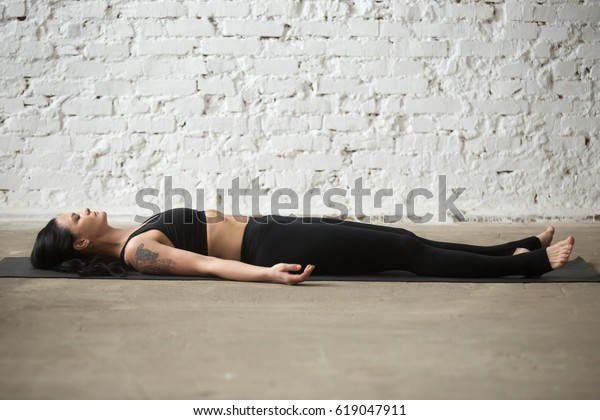 Young yogi attractive woman practicing yoga concept, lying in Savasana exercise, Corpse, Dead Body pose on floor, working out wearing black sportswear top and pants, full length, white loft background