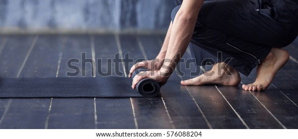 Young yogi men rolling mat after a yoga on black wooden floor. Close up of man hands with black mat, copy space. Healthy Fitness background. Banner and mock up concept