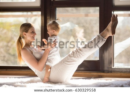 Young yogi smiling mother working out engaging her playful child, toning abs muscles, , integrating baby into yoga practice, fitness at home when having no time for gym. Healthy lifestyle concept