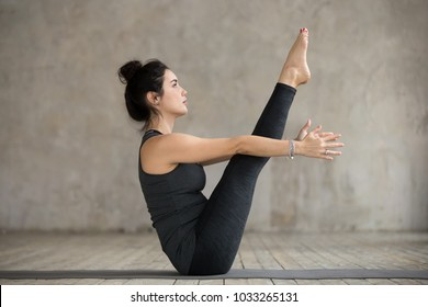 Young yogi woman practicing yoga, doing Paripurna Navasana exercise, boat pose, working out, wearing sportswear, black pants and top, indoor full length, gray wall in yoga studio