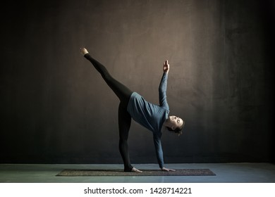 Young yogi woman practicing yoga in Half Moon exercise, Ardha Chandrasana pose. Indoor full length, black background