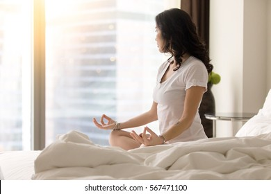 Young yogi woman practicing yoga after waking up, sitting in Padmasana exercise on unmade bed, Lotus pose on meditation session, working out wearing white casual clothes, looking at window. Copy space