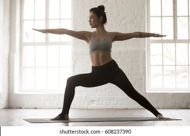 Young yogi woman practicing yoga, standing in Warrior two exercise, Virabhadrasana II pose, working out wearing sportswear bra and pants, full length, white loft studio background. Weight loss concept