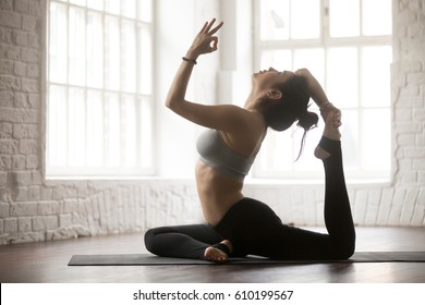 Young yogi woman practicing yoga concept, doing One Legged King Pigeon exercise, Eka Pada Rajakapotasana pose, working out, wearing sportswear bra and pants, silhouette, white loft studio background