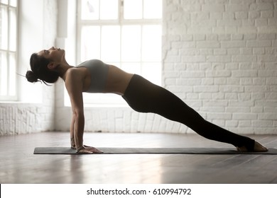 Young yogi woman practicing yoga concept, doing Purvottanasana exercise, Upward Plank pose, working out, wearing sportswear, full length, white loft studio background, side view. Weight loss concept
