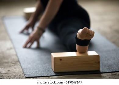 Young yogi woman practicing yoga concept, doing advanced splits, Straight Angle exercise, Samakonasana pose using blocks for deep stretch, working out on mat wearing black pants, leg close up, studio