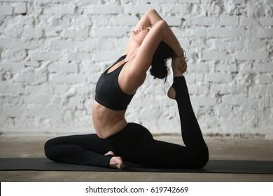 Young yogi woman practicing yoga concept, sitting in One Legged King Pigeon exercise, Eka Pada Rajakapotasana pose, working out, wearing black sportswear, full length, white loft background. Side view