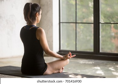 Young yogi woman practicing yoga at home, sitting in Sukhasana exercise, Easy Seat pose with mudra, working out, wearing sportswear, black shorts, top, indoor full length, window background, rear view
