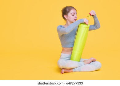 Young yogini woman before yoga glass sitting in lotus pose unpacking her mat