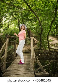 Young youful woman with sunhat posing on the wooden bridge. Beauty and nature.