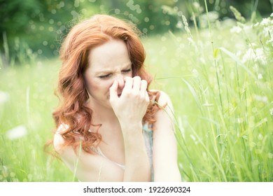 Young,beautiful,redheaded woman in spring sitting in tall grass with allergy and hay fever.