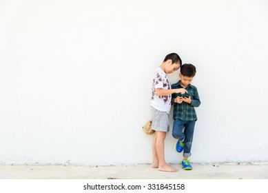 Younger Asian boy play smartphone but another poor boy looks unhappy and lonely at the white wall. Social network concept.
