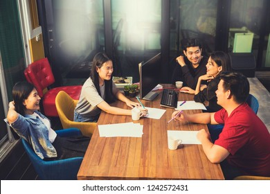 younger asian freelance team relaxing on working table in office meeting room