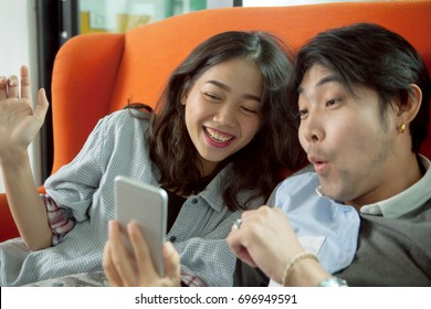 younger asian man and woman happiness emotion when looking on smart phone screen