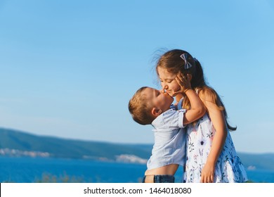 younger brother kissing sister and holding her face in hands at sunset