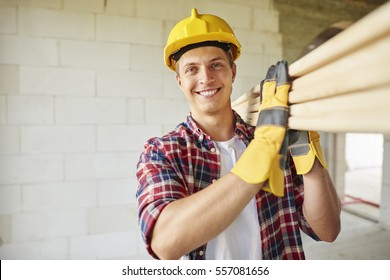 Younger carpenter holds wooden planks