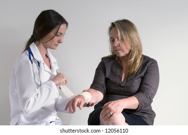 Younger female doctor wrapping the wrist of an older female patient with a bandage