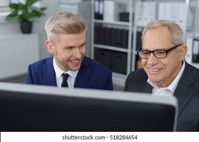 Younger and older man in formal business attire seated behind computer monitor in small office