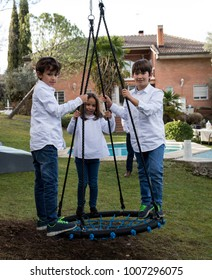 younger siblings playing in the backyard on a swing