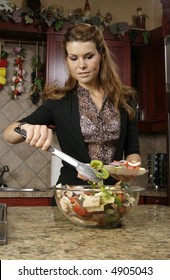 Younger woman serving vegetable salad from large glass bowl onto plate.