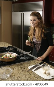 Younger woman snaking on vegetable as she prepares meal in a kitchen.