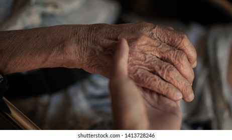 A youngster holding elderly hand with care