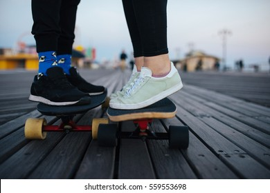 Youngsters on the longboards on boardwalk, riding together