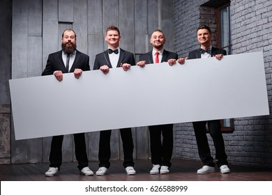 Your advertisement in good hands. Group of handsome young men in tuxedo holding big blank with copy space.
