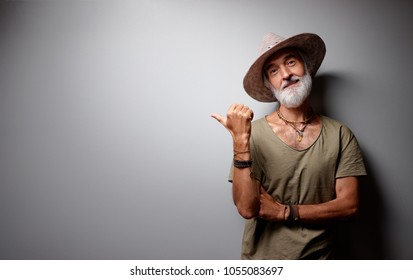 Your advertising here. Studio portrait of handsome senior man with gray beard and hat showing copy space on wall.