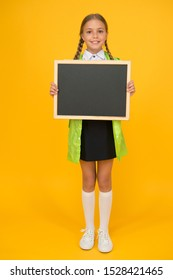 For your attention. Happy girl hold school blackboard on yellow background. Small child with blank blackboard. Little schoolchild got blackboard for lesson. Blackboard for school advert, copy space.