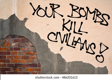 Your Bombs Kill Civilians - Handwritten graffiti sprayed on wall, anarchist aesthetics - protest against collateral damage during war in warzone. Fight against unintentional killing and victims