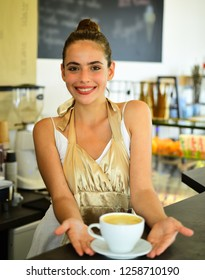 Your cup of inspiration. Happy woman barista in coffee shop. Pretty woman stand behind cafe counter. Adorable barista serve cup of hot coffee drink with smile. Brewing coffee in coffeehouse.